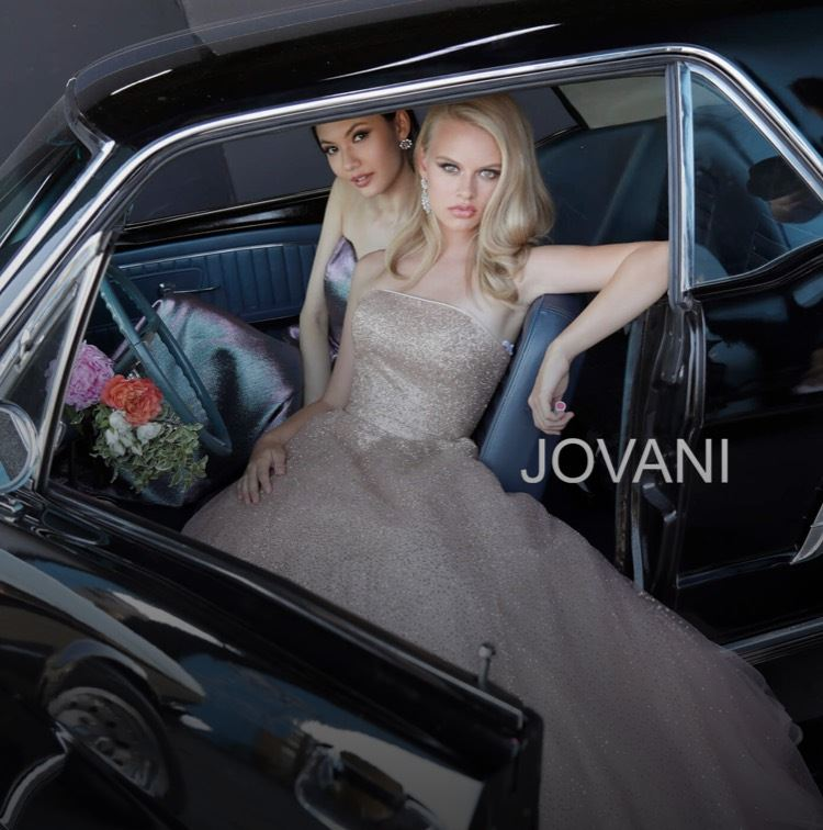 Two models in Jovani dresses sitting in a car